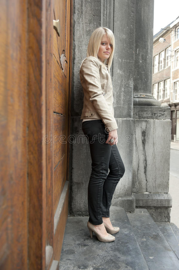 Young blond woman standing against a door stock images