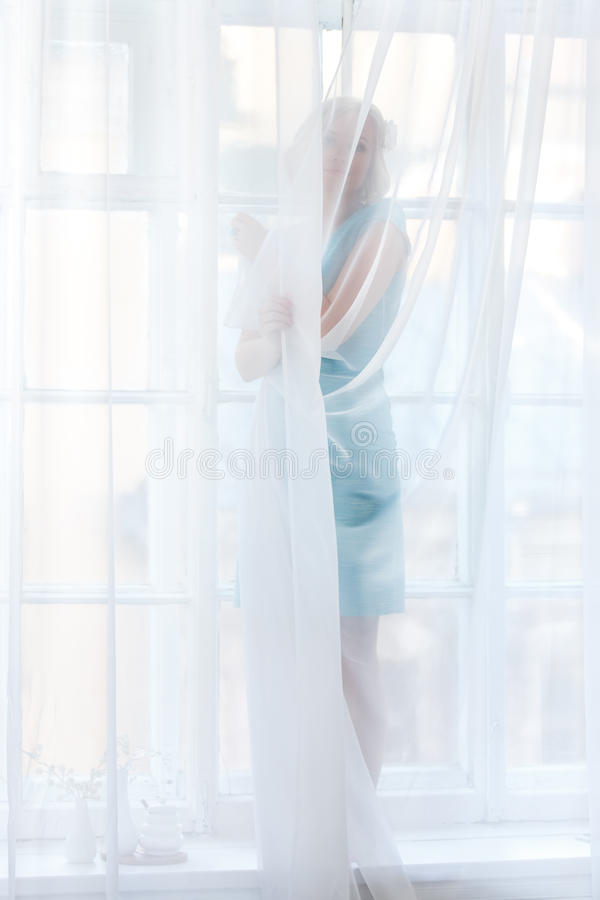 Young blond woman standing behind transparent white curtains royalty free stock photos
