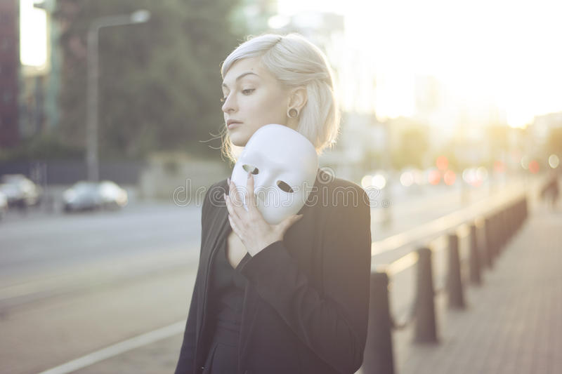 Young blond woman taking off a mask. Pretending to be someone else concept. outdoors on sunset. royalty free stock photos