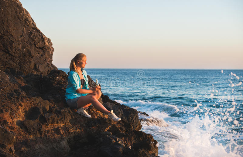 Young blond woman tourist with glass bottle of lemonade sittig on rocks by the sea at sunset. Alanya, Mediterranean royalty free stock image