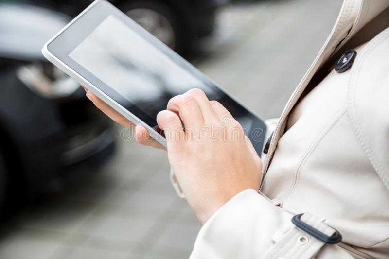 Young blond woman using a tablet outdoors stock photo