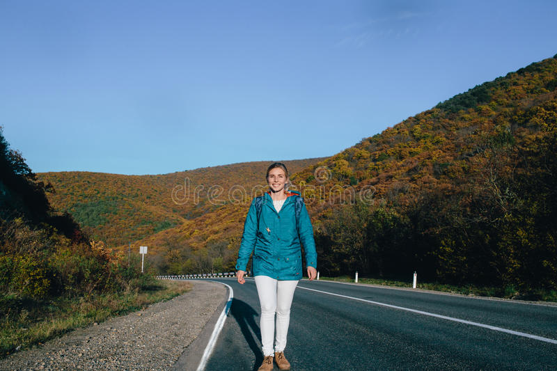 Young blond woman walking along an empty road. Adventure and tourism concept royalty free stock photo
