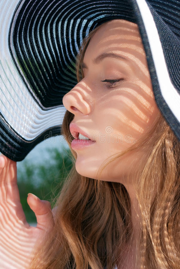 Young blond woman wearing black and white hat royalty free stock photography
