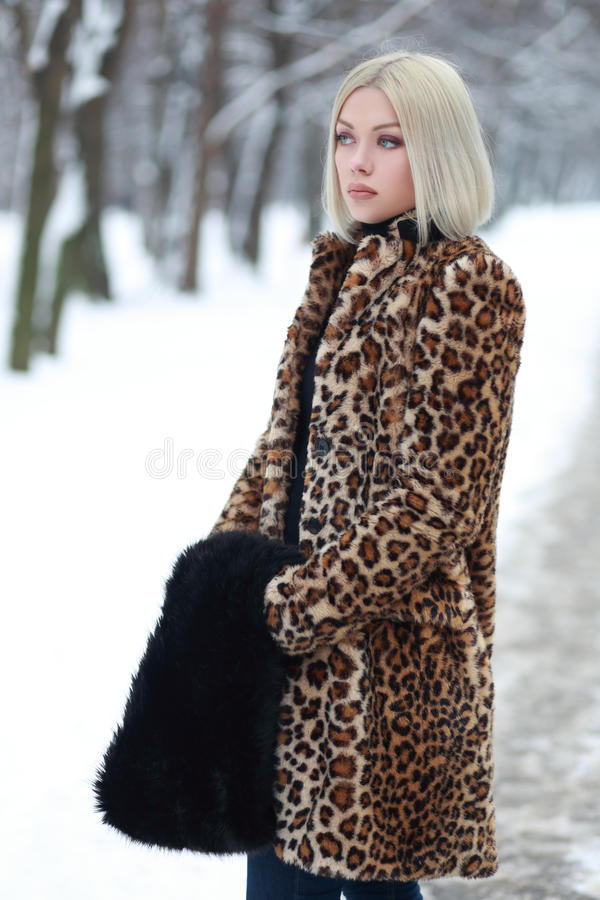 Young blond woman winter park. Young blond woman in winter park weared in furry coat stock images
