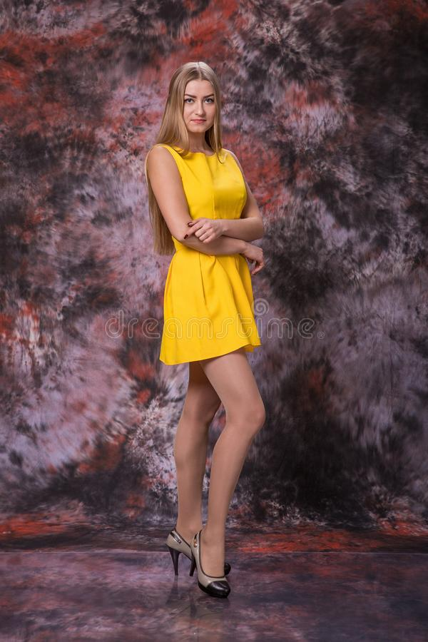 Blond woman in yellow dress on marble multicolored background. Model test. stock photos
