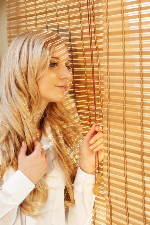 Young happy woman looking out the window through the blinds. Young blonde beautiful happy woman looking out the window through the bamboo blinds with Sun royalty free stock photo