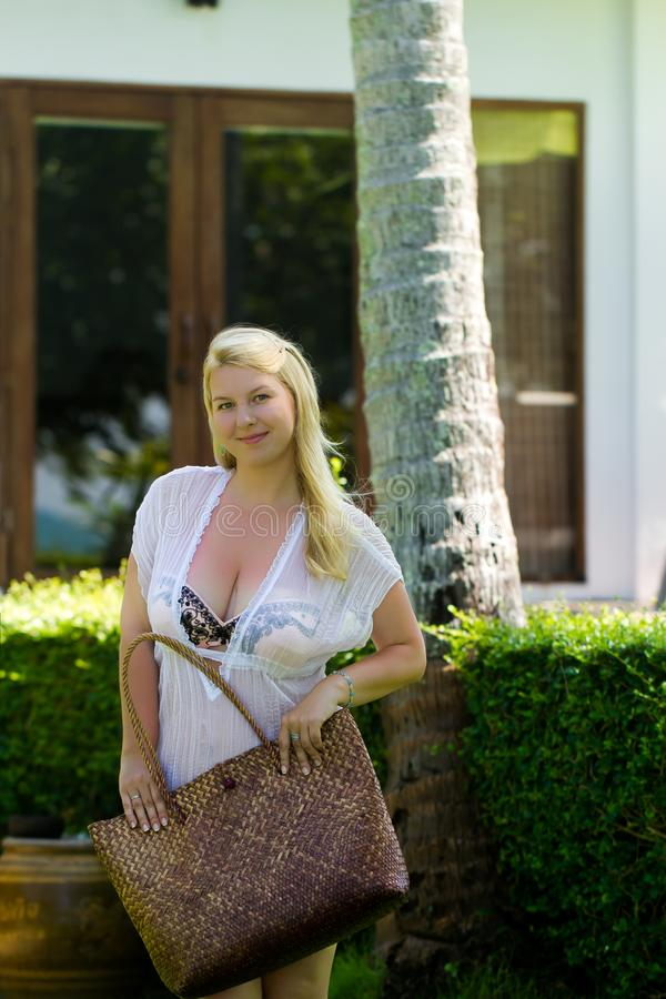 Young blonde beautiful woman in see-through beach dress and bikini near luxury tropical villa with big bag going to. Shopping or sunbathe posing royalty free stock image