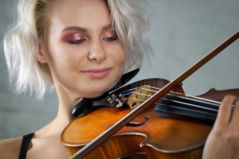 Young blonde beautiful woman violinist plays violin close up stock photography