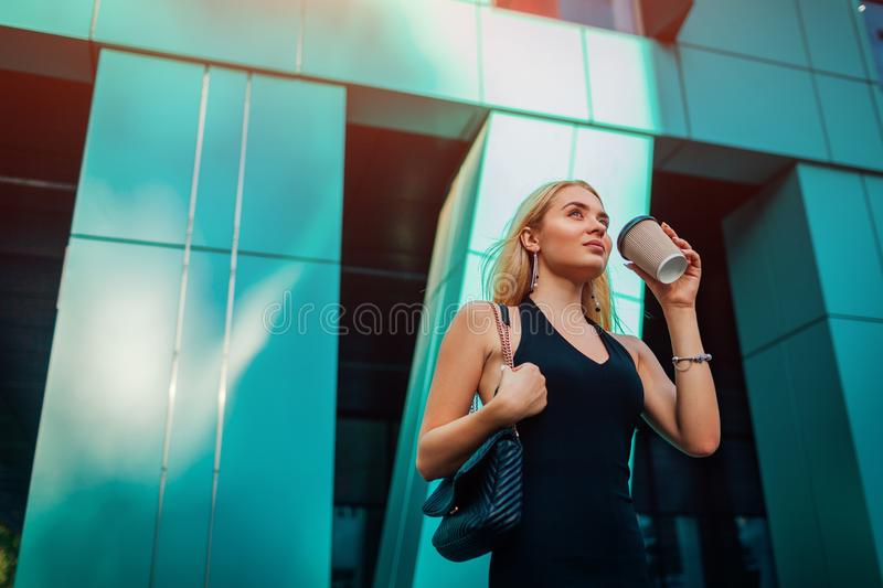 Young blonde businesswoman having coffe break by modern business center in city. Portrait of stylish successful woman royalty free stock images