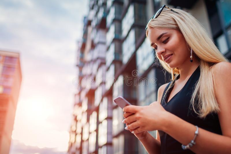 Young blonde businesswoman using smartphone by contemporary business center in city. Communiation royalty free stock photos