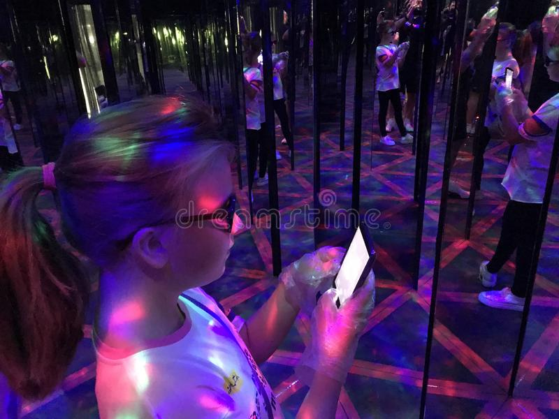 A young girl taking a selfie in hall of mirrors royalty free stock photos