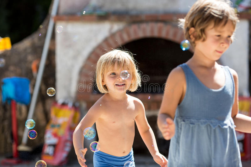 Young blonde child girl with friend or sister playing with soap bubbles. Warm sunset light. Family summer trave royalty free stock photography