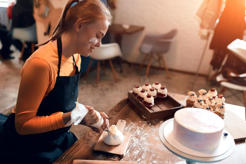 Young blonde cook is good at decorating dessert. close up side view photo stock photo