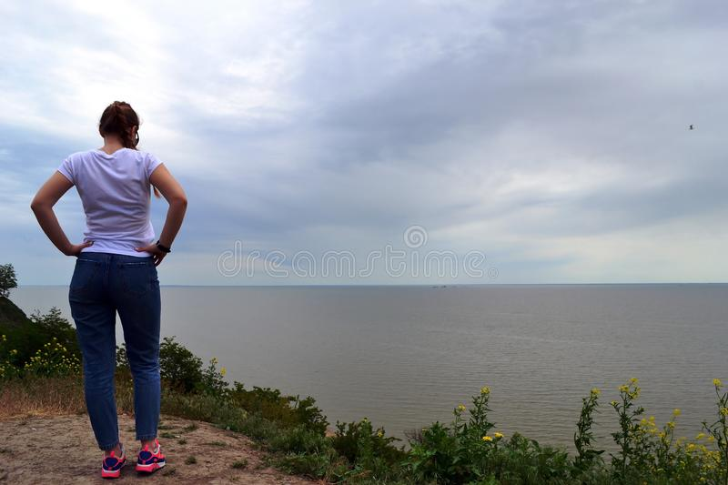Young blonde curly girl looking at hazy sunshine through a thick mist on a calm sea and blue skies back view. Blue sky royalty free stock photo