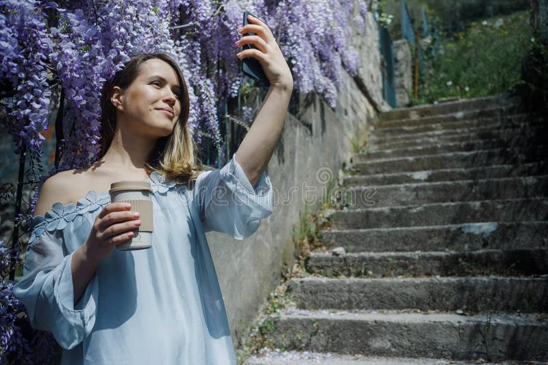 Young blonde curly hair woman in blooming wisteria garden in spring. Woman wearing in lilac dress making selfie on smartphone royalty free stock photos