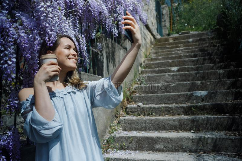 Young blonde curly hair woman in blooming wisteria garden in spring. Woman wearing in lilac dress making selfie on smartphone stock image