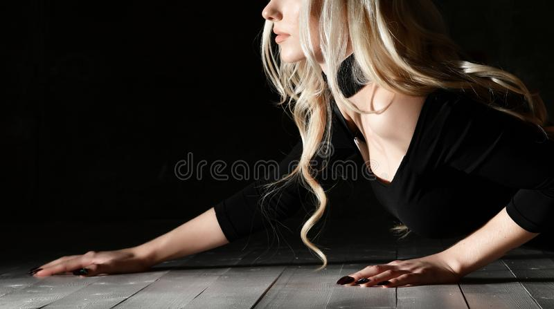 Young blonde fashion woman lying on floor in black body cloth and choker stock photos
