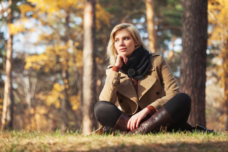 Young fashion woman in beige coat sitting on grass in autumn park royalty free stock images