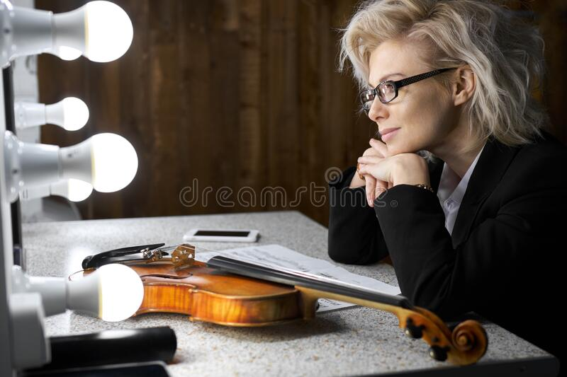 Young blonde female violinist dreaming sitting at the table. Young blonde female violinist wearing eyeglasses dreaming sitting in the dressing room before the royalty free stock photography