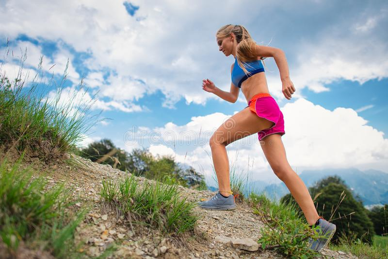 Young blonde girl athlete running in the mountains uphill on trail royalty free stock images