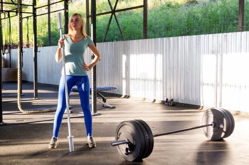 Young blonde girl in blue leggings and a green T-shirt is standing in the gym outdoors, holding a barbell bar in the background o stock photography