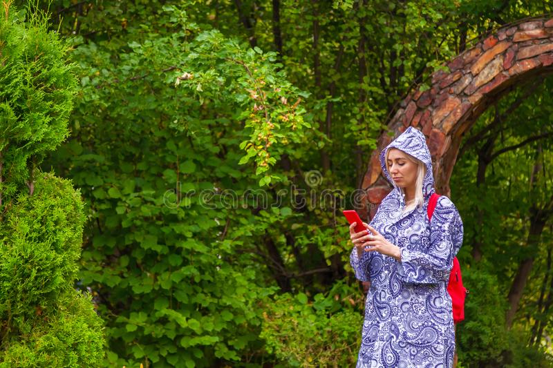 A young blonde girl in a blue raincoat with a red backpack on her back, a phone in her hand walks along a path in stone arch royalty free stock photography