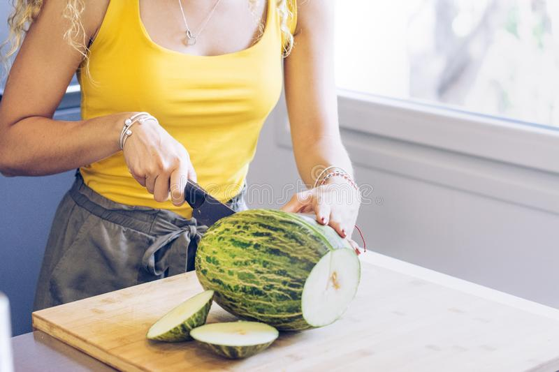 Young blonde girl cutting a melon. With a knife, in the kitchen by a window royalty free stock photo