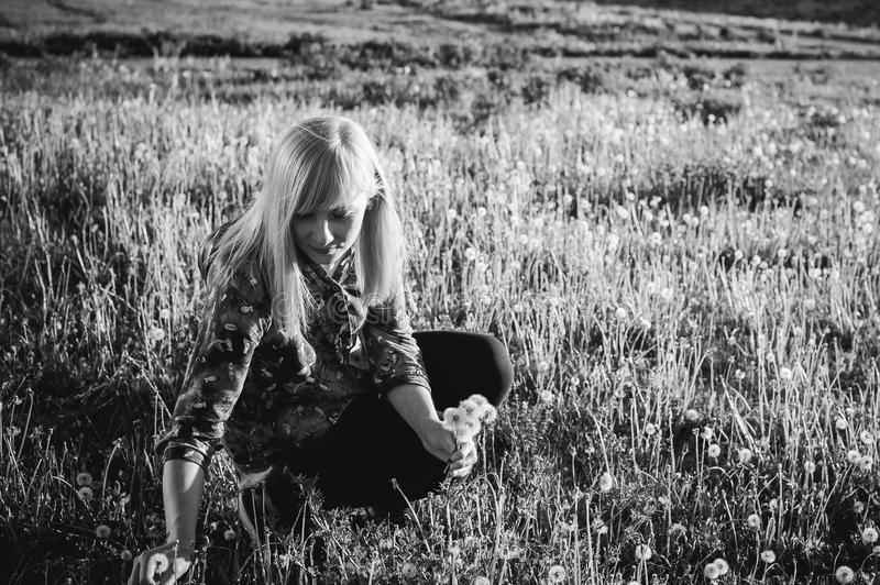 Young blonde girl in dress with shoulder bag, walking on dandelion field stock photos