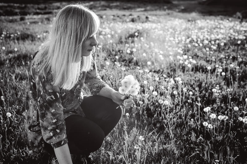 Young blonde girl in dress with shoulder bag, walking on dandelion field royalty free stock image