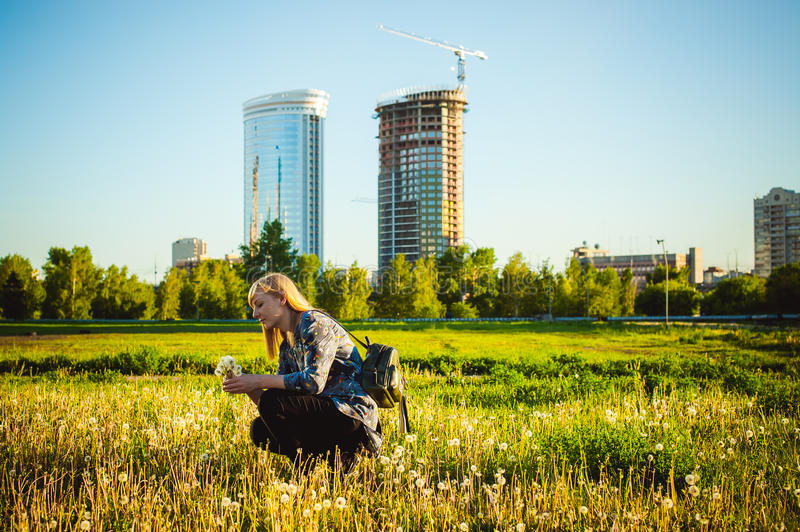 Young blonde girl in dress with shoulder bag, walking on dandelion field royalty free stock photography