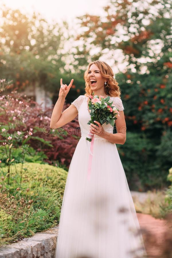 Young blonde girl in an elegant long white light dress is joking laughing at the camera in a green garden, holding a royalty free stock photography