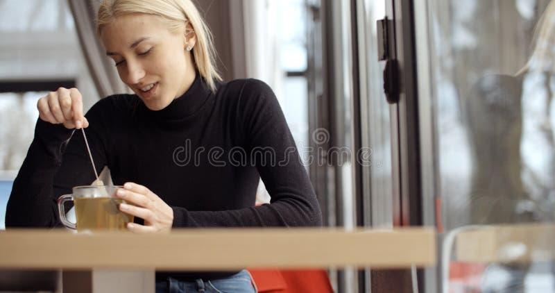 Young blonde girl enjoying her tea in restaurant. royalty free stock photos