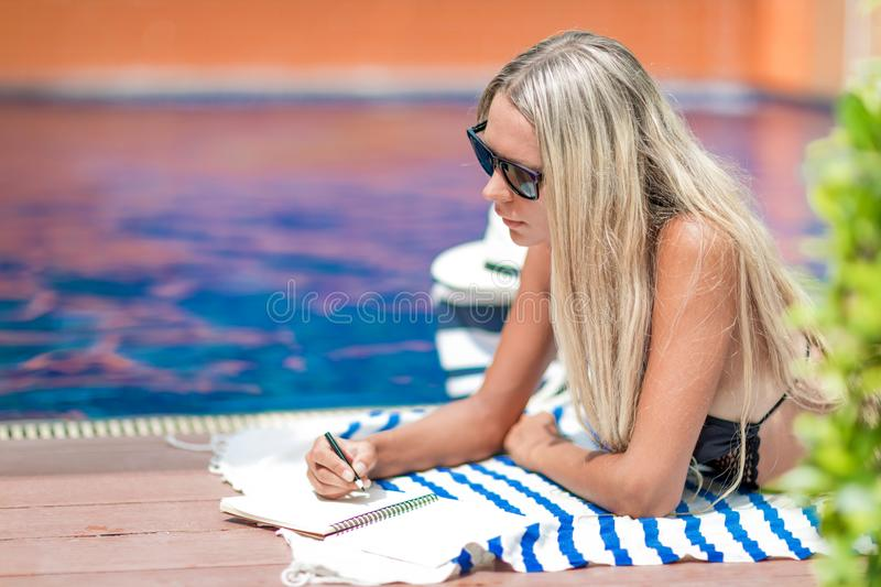 Young blonde girl freelancer in bikini works near swimming pool, writes in note book, getting sun tan royalty free stock photos