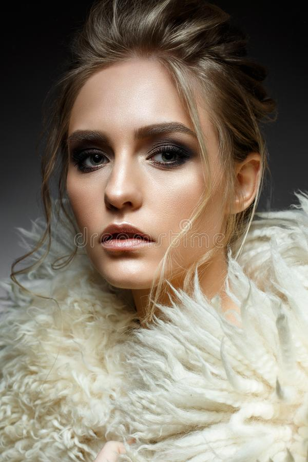 Young blonde girl with hairdo and creative makeup. Beautiful model in a fur coat. Shining skin. Evening image. Beauty of the face royalty free stock images