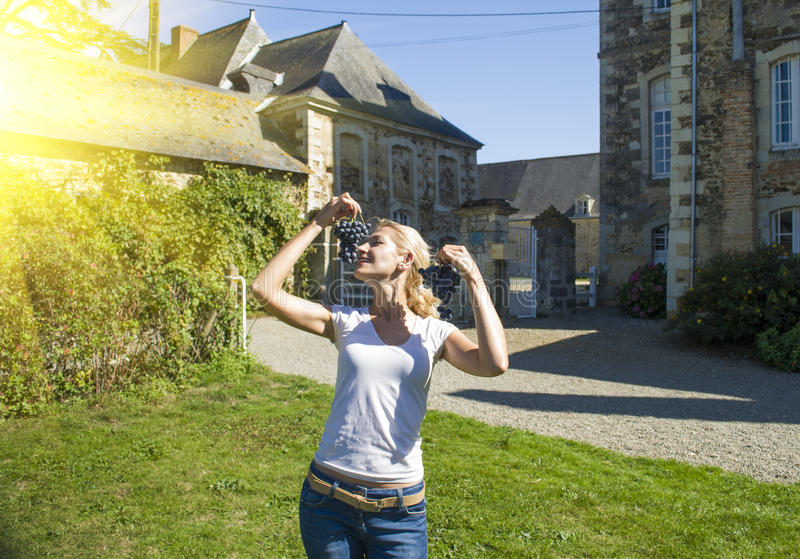 Young blonde girl holding grape in front of old French buildings in Provence. PYoung blonde girl holding grape in front of old French buildings in Provence royalty free stock images