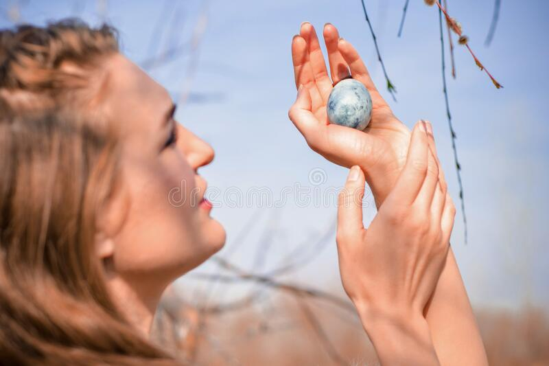 Young blonde girl, holds blue egg in hands, like dragon egg from fantasy, against blue sky, like mother of dragons. Young blonde girl in a light dress, holds a stock image