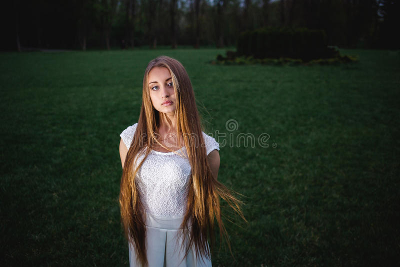 Young blonde girl illuminated by a magic lantern in the night mystery garden royalty free stock image