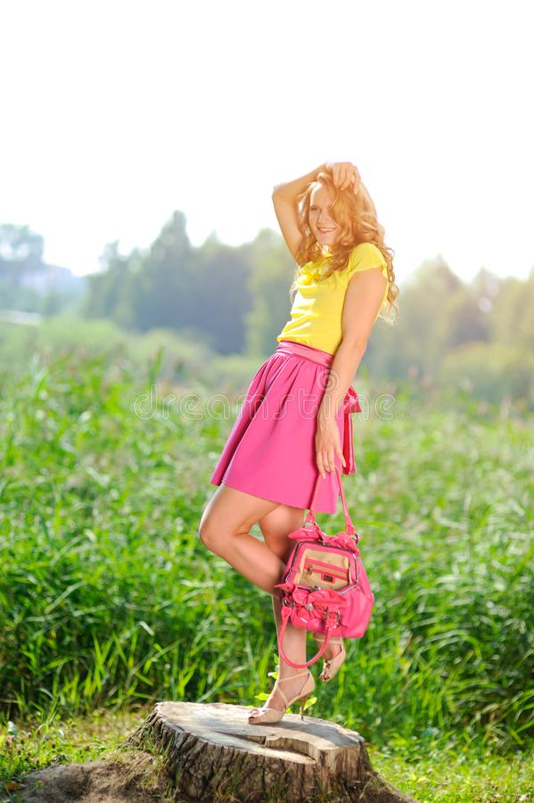 Free Young Blonde Girl In A Yellow Blouse With A Bright Pink Skirt Posing In A Summer Park In The Rays Of A Bright Sun Stock Photo - 106886180
