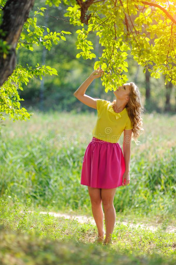 Free Young Blonde Girl In A Yellow Blouse With A Bright Pink Skirt Posing In A Summer Park In The Rays Of A Bright Sun Stock Photography - 106886272