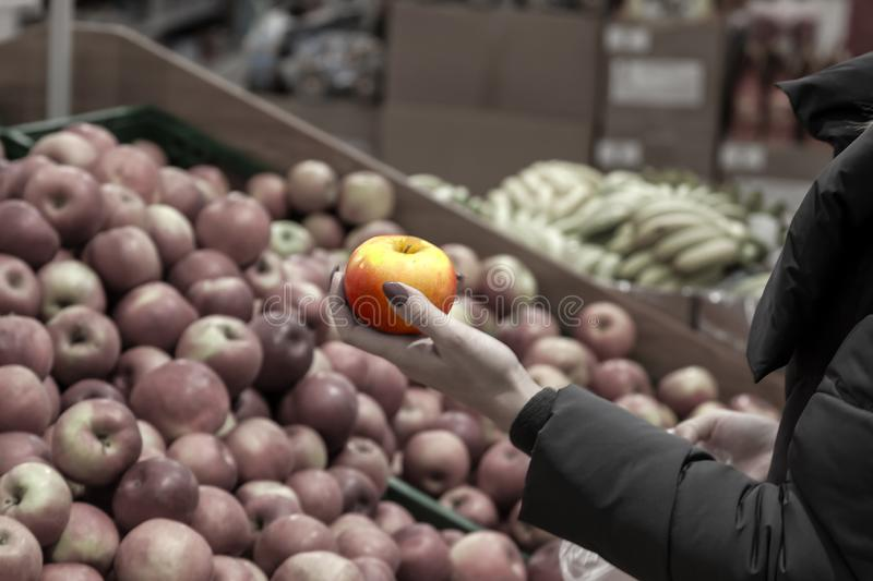 A young blonde girl in a long jacket chooses food while shopping stock photos