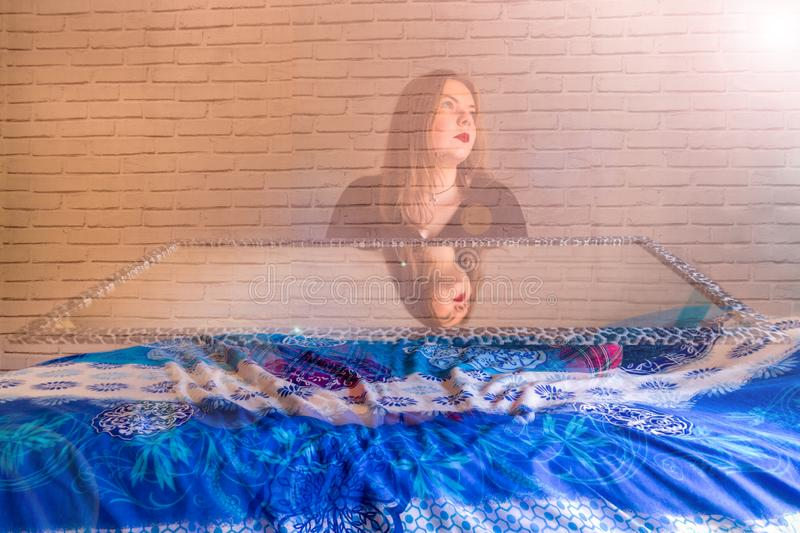 Young blonde girl with a mirror, with half of the body erased royalty free stock image