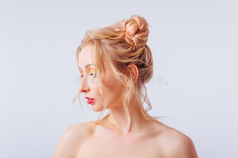 Young blonde girl with an original hairstyle and bright professional makeup royalty free stock photography