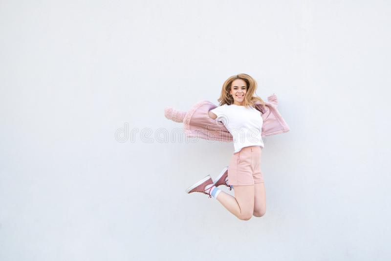 Young blonde girl in pink clothes jumping against the background of a white wall and smiling stock image