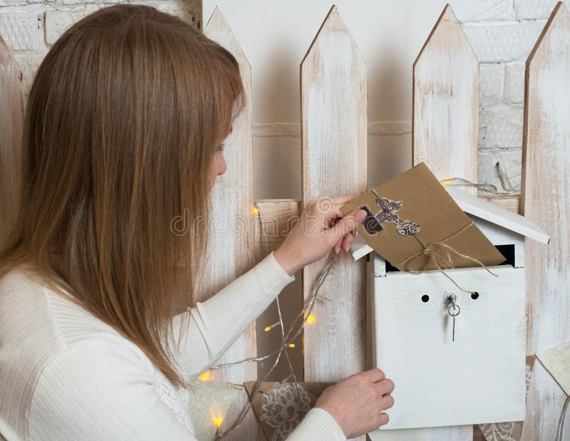 A young blonde girl puts an envelope with a letter in a box for desires. royalty free stock photo