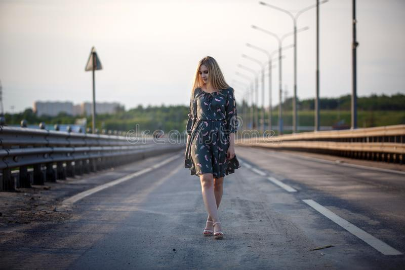 Young blonde girl on the road in the evening soft light of the sun. A girl in a green dress with long hair, the dress is blown by the wind royalty free stock photos