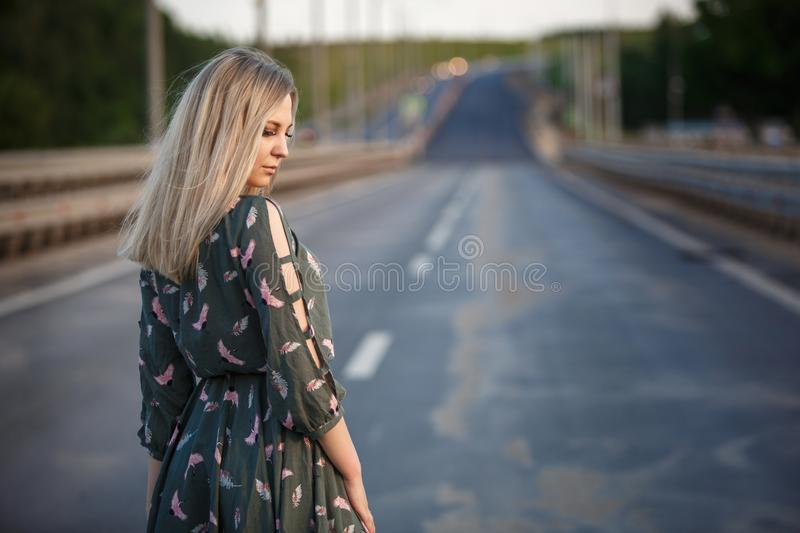Young blonde girl on the road in the evening soft light of the sun. A girl in a green dress with long hair, the dress is blown by the wind stock images