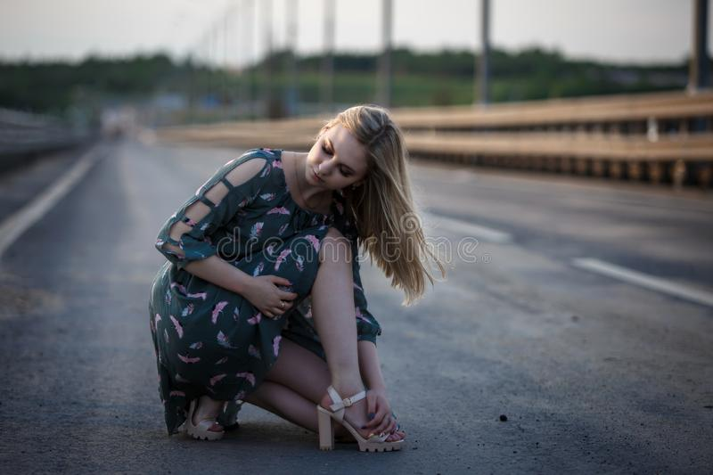 Young blonde girl on the road in the evening soft light of the sun. A girl in a green dress with long hair, the dress is blown by the wind royalty free stock photography
