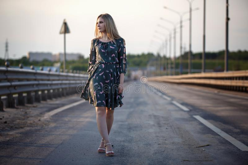 Young blonde girl on the road in the evening soft light of the sun. A girl in a green dress with long hair, the dress is blown by the wind royalty free stock photo