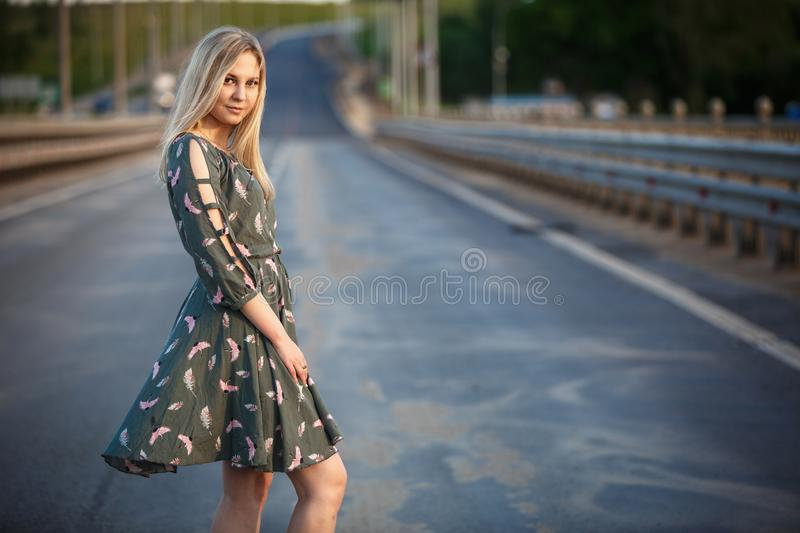 Young blonde girl on the road in the evening soft light of the sun. A girl in a green dress with long hair, the dress is blown by the wind stock photo