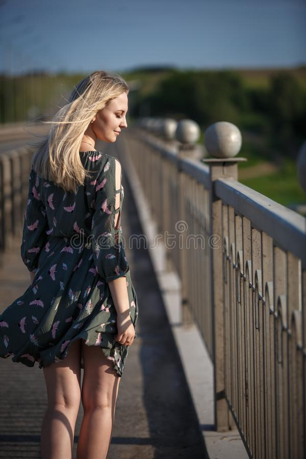 Young blonde girl on the road in the evening soft light of the sun. A girl in a green dress with long hair, the dress is blown by the wind stock photography